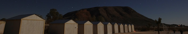In Landers, California, a row of observatories stand watch over GMARS on a moon-filled night.